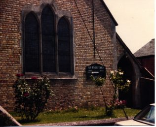 Exterior photo of Islip Methodist church with rose bushes in bloom in front.