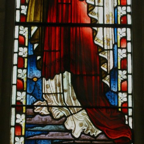Stained glass of female figure representing charity or love.