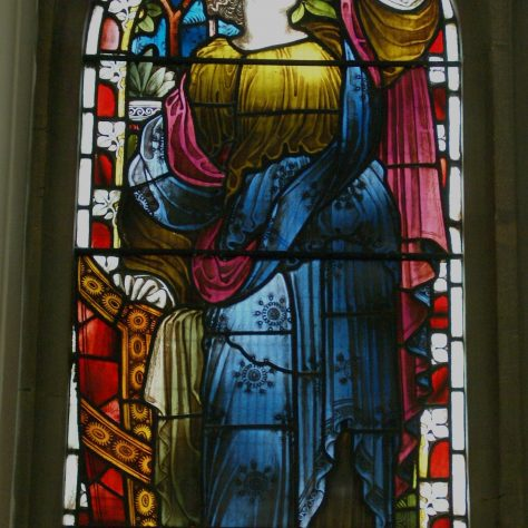 Stained glass window of female figure representing faith