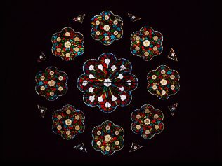 Stained glass in a rose formation featuring white lilies and roses on a red and blue background